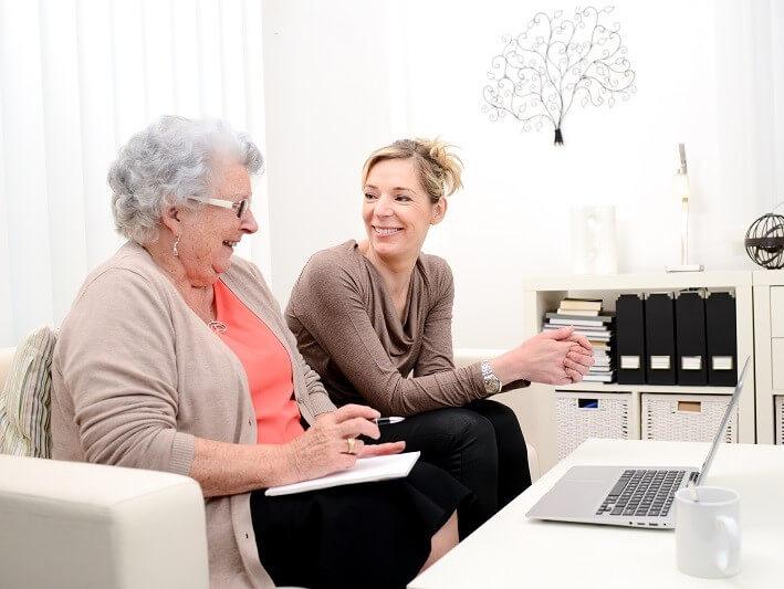 Een oudere en jongere vrouw kijken naar het beeldscherm van een laptop